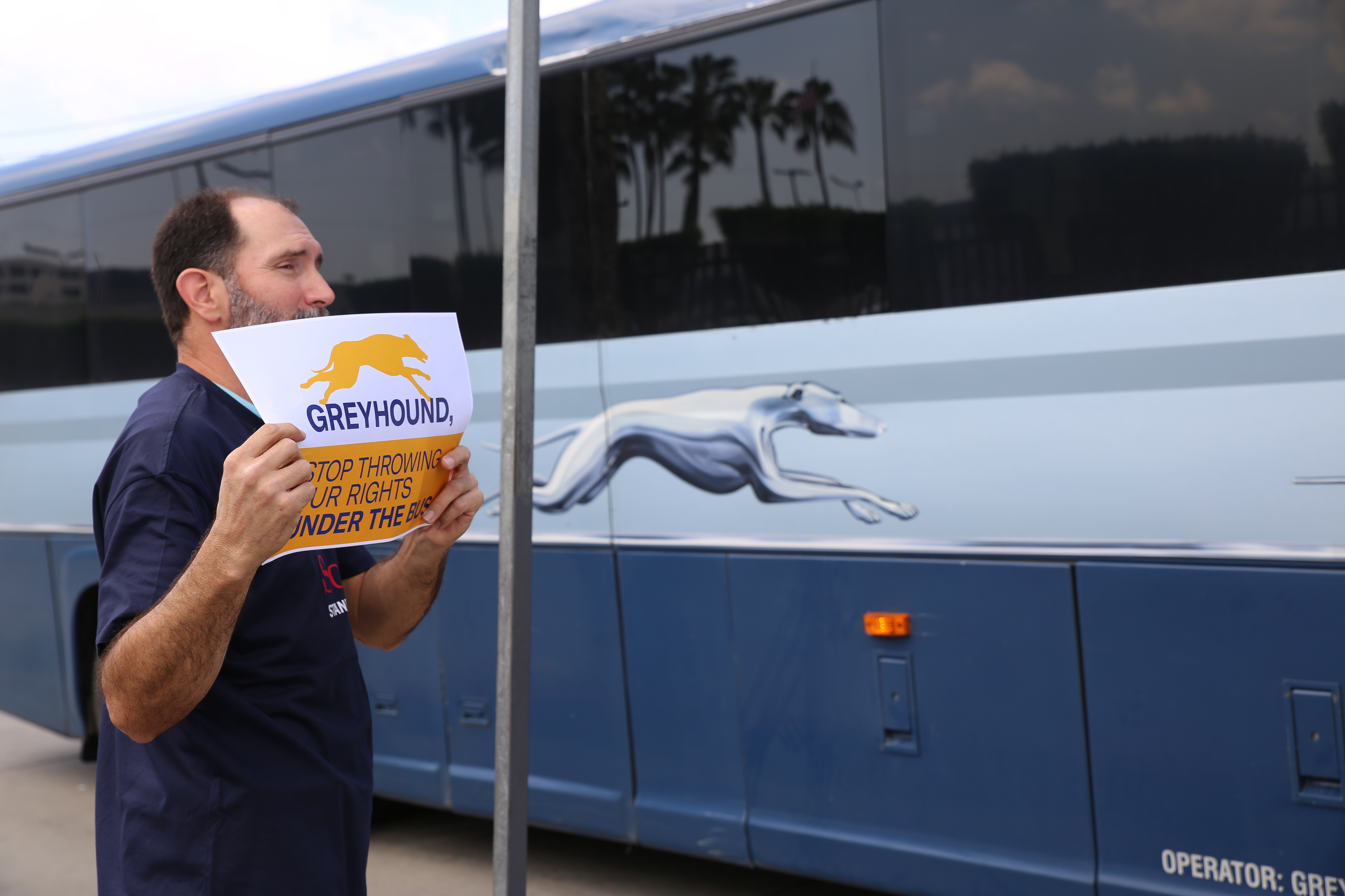 """A man on the sidewalk holding a sign that reads """"Greyhound, stop throwing our rights under the bus"""" as a Greyhound bus passes by."""
