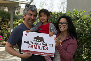 A family, a man woman and young daughter, all holding a sign that reads California Values Families.