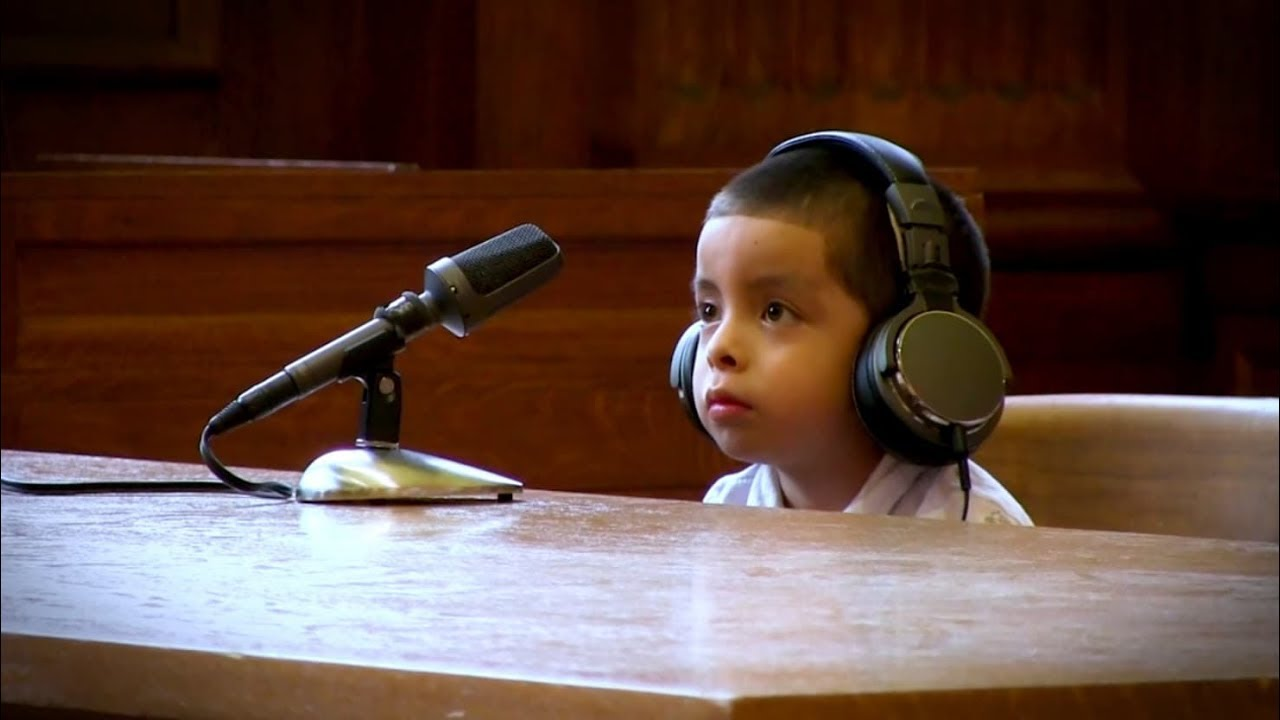 Young child in court wearing headphones, sitting at a table with a microphone in front of him.