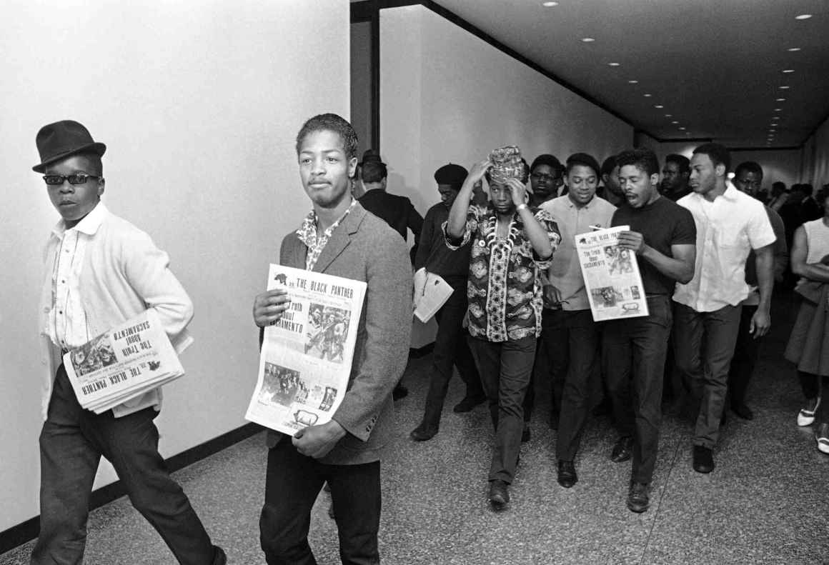 Members of the Black Panther Party walking down a hallway, holding newspapers.