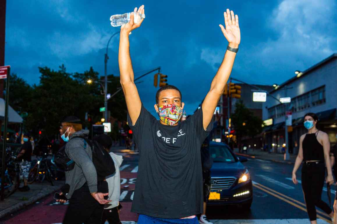 A man at a protest against police violence holding his hands in the air.