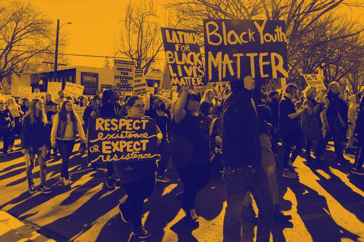 "Large group of people protesting, walking down the street holding signs that read ""Black Youth Matter,"" ""Latinos for Black Lives Matter,"" ""Respect existence or expect resistance"""