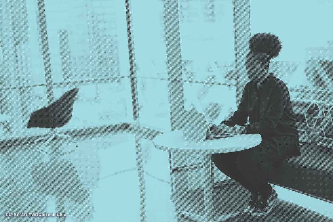 A young Black woman with an afro puff sitting on a sofa, using her laptop at a small table. Image courtesy of #WOCinTech Chat.