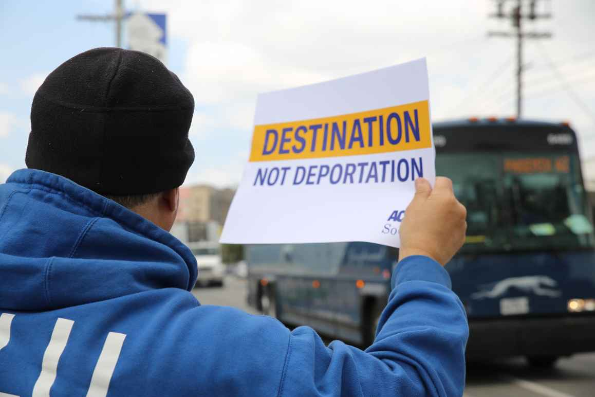 "Man on sidewalk, holding a sign as a  Greyhound bus passes by: ""Destination not deportation"""