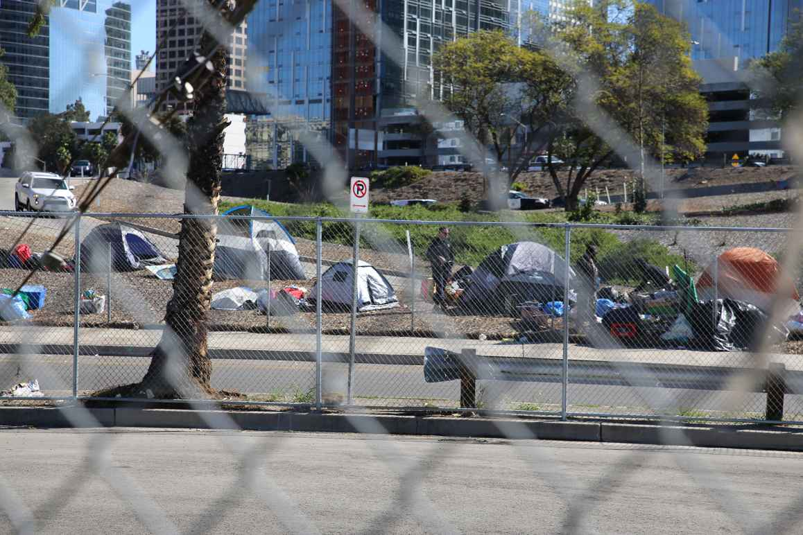 A police officer standing next to a group of tents to the side of a freeway on-ramp