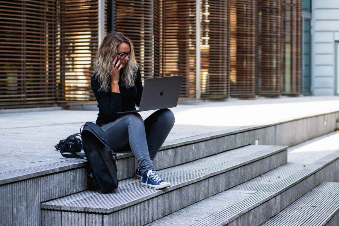 A young woman with shoulder length blonde hair, sitting on the steps of a large building, with a cell phone to her ear and a laptop propped on her knees, a backpack next to her on the ground.