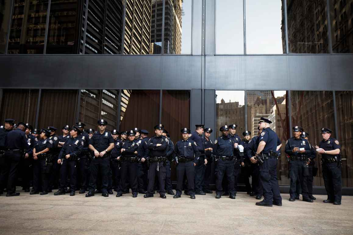 A large group of police officers standing in front of a building