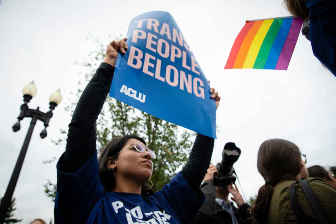 "A young woman holding a poster that reads ""Trans people belong."" Copyright ACLU/Molly Kaplan"