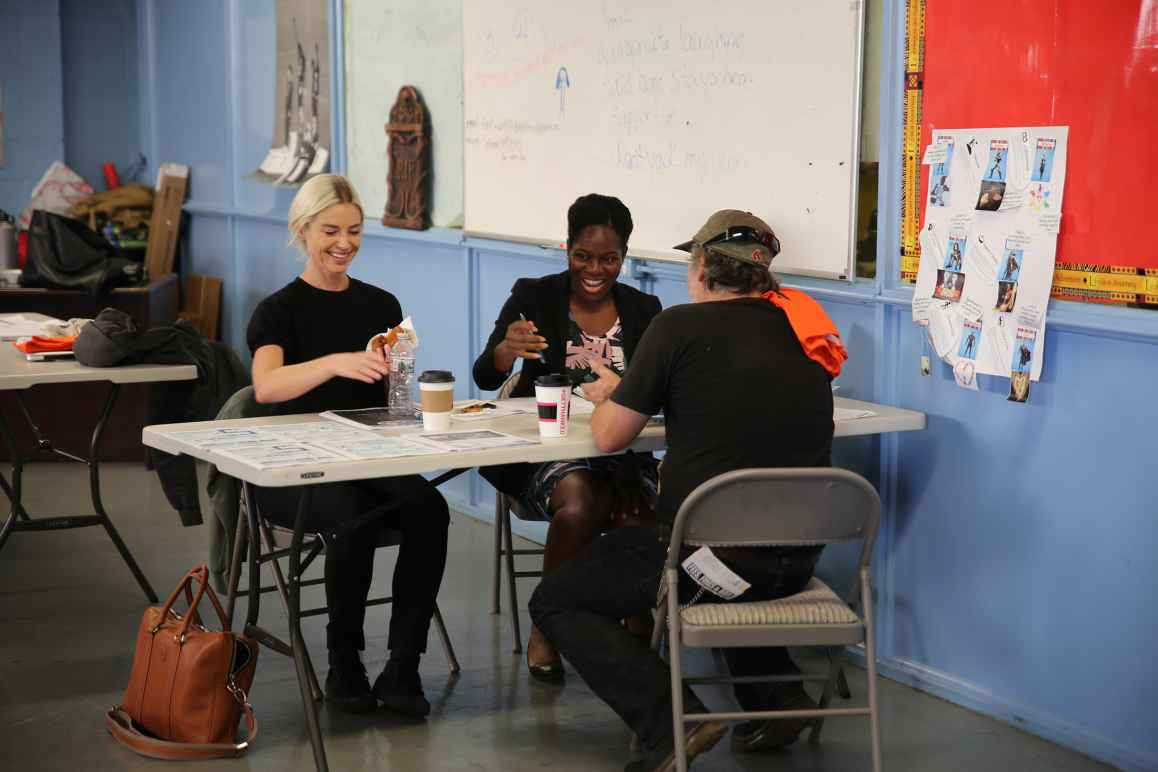 Three people sitting around a table at a community event working together.