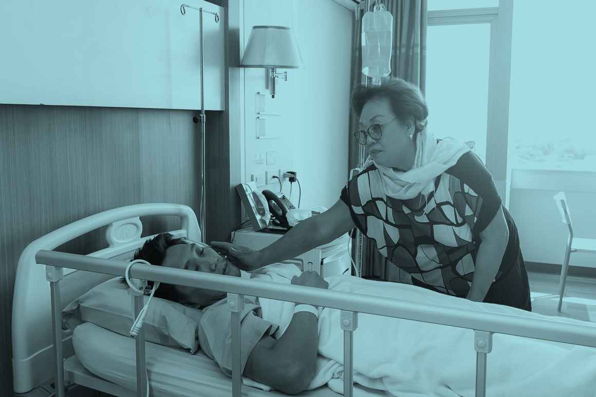 A woman at the hospital bedside of a man