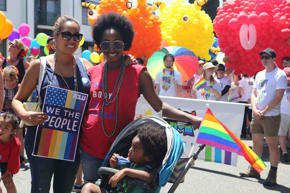 Two women with a child in a stroller in the foreground at a Pride Parade. One woman is holding a sign that reads We the People.