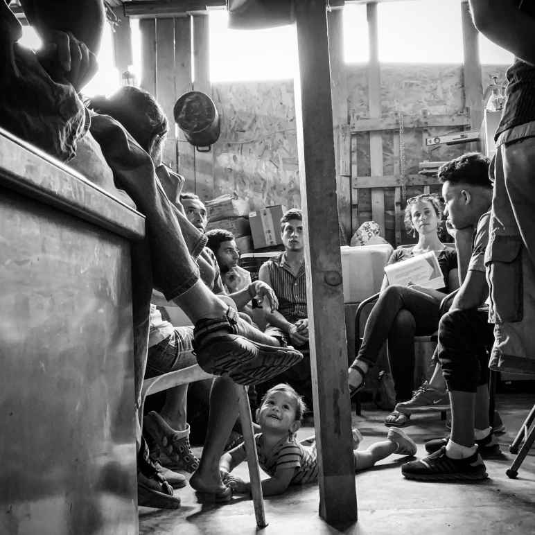 Ana Adlerstein sitting with a small group of Central American migrants in a room, a toddler is crawling on the floor looking up at a seated adult