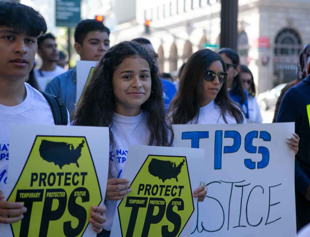 """Crista Ramos and TPS rally attendees hold up signs that say, """"Protect TPS."""""""