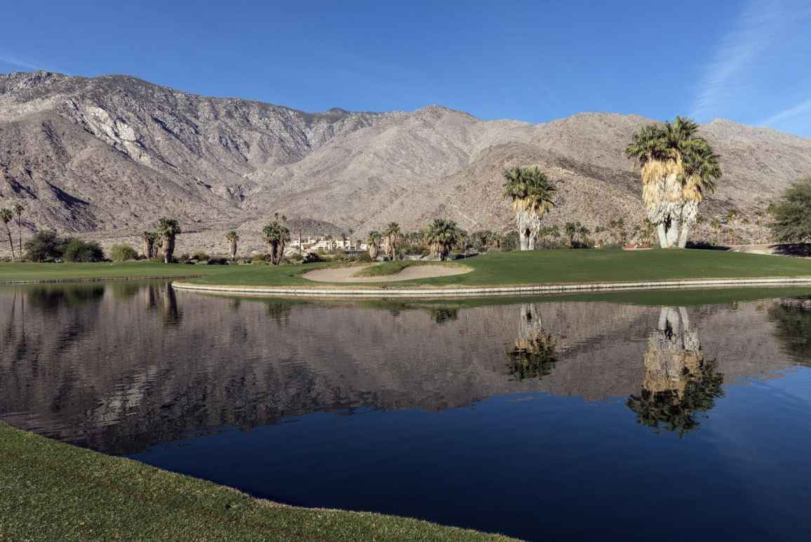 Golf course in Coachella Valley, a pond in the foreground, palm trees and mountain range in the background