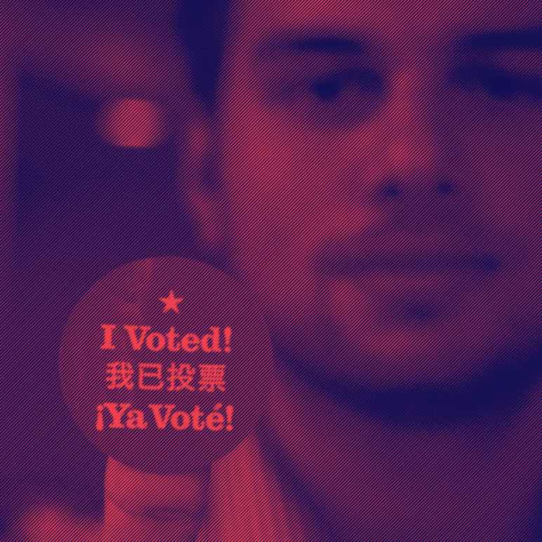 Man holding up a round sticker with text that reads: I voted!