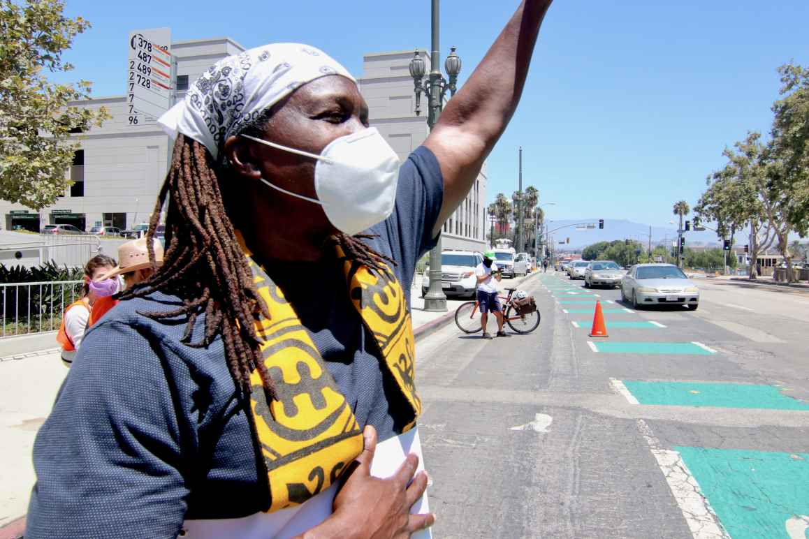 A Black clergy member, wearing a face mask, protesting in the street with their arm raised
