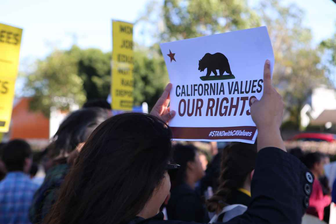 Woman in crowd holding a sign above her head that reads: California values our rights
