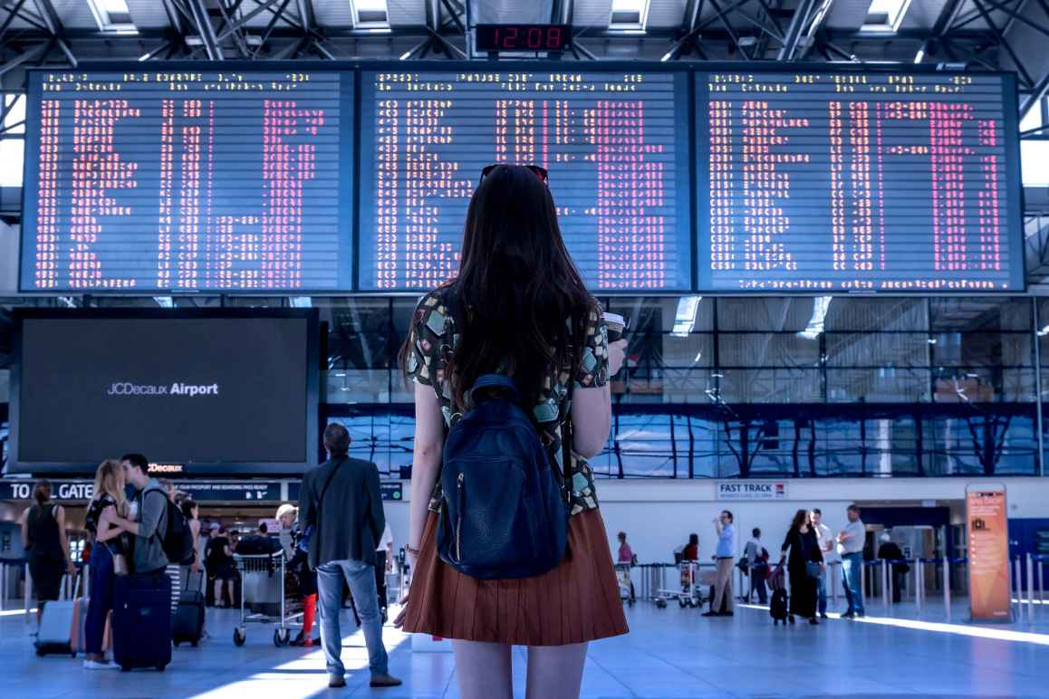 A woman at the airport looking up at the arrivals/departures board