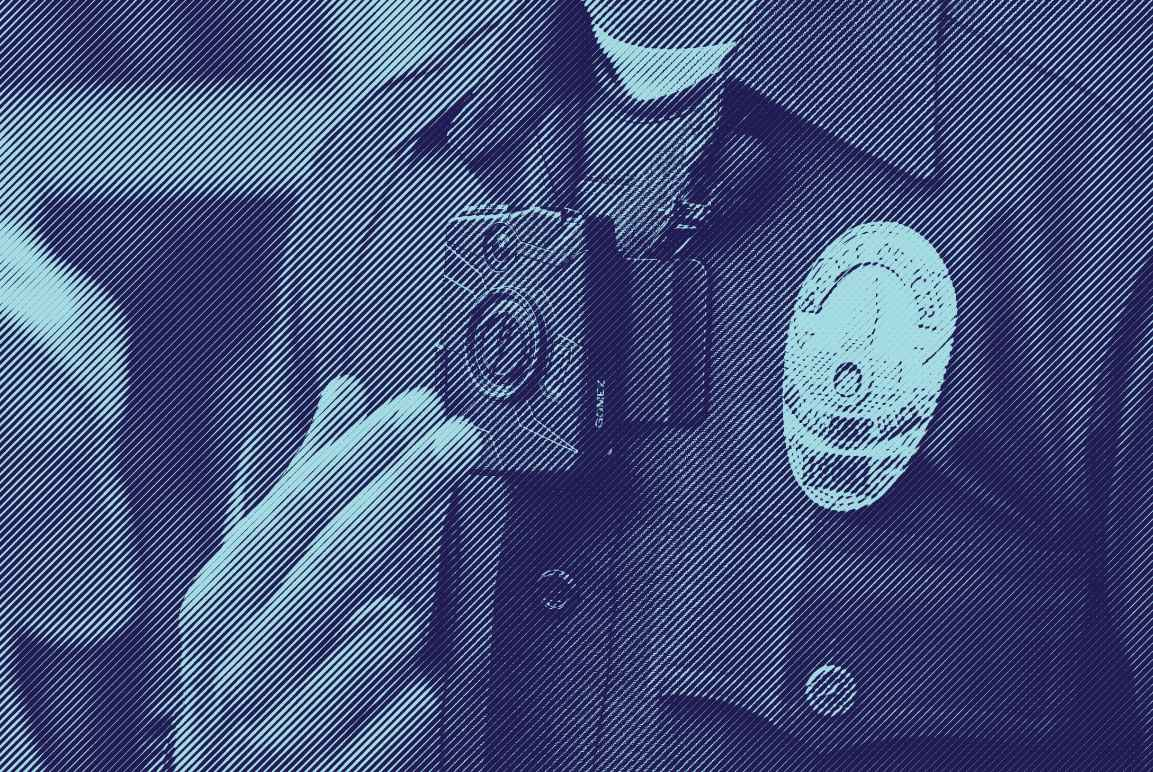 Close up photo of a police man wearing a body camera near his lapel, next to his police badge