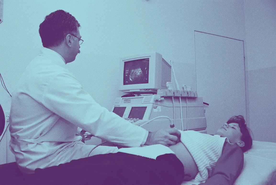 A woman lying on an exam table, a male doctor performing an ultrasound by placing a wand over her abdominal area