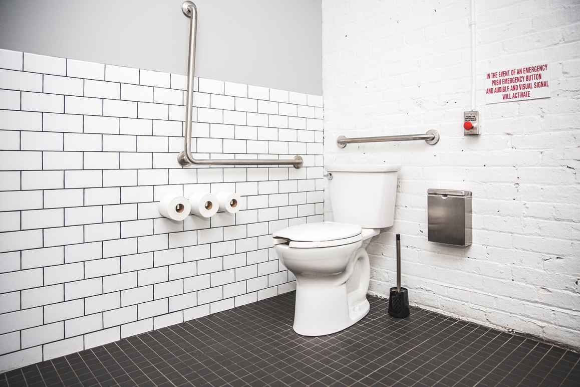 restroom stall with a toilet, toilet paper, grab bar
