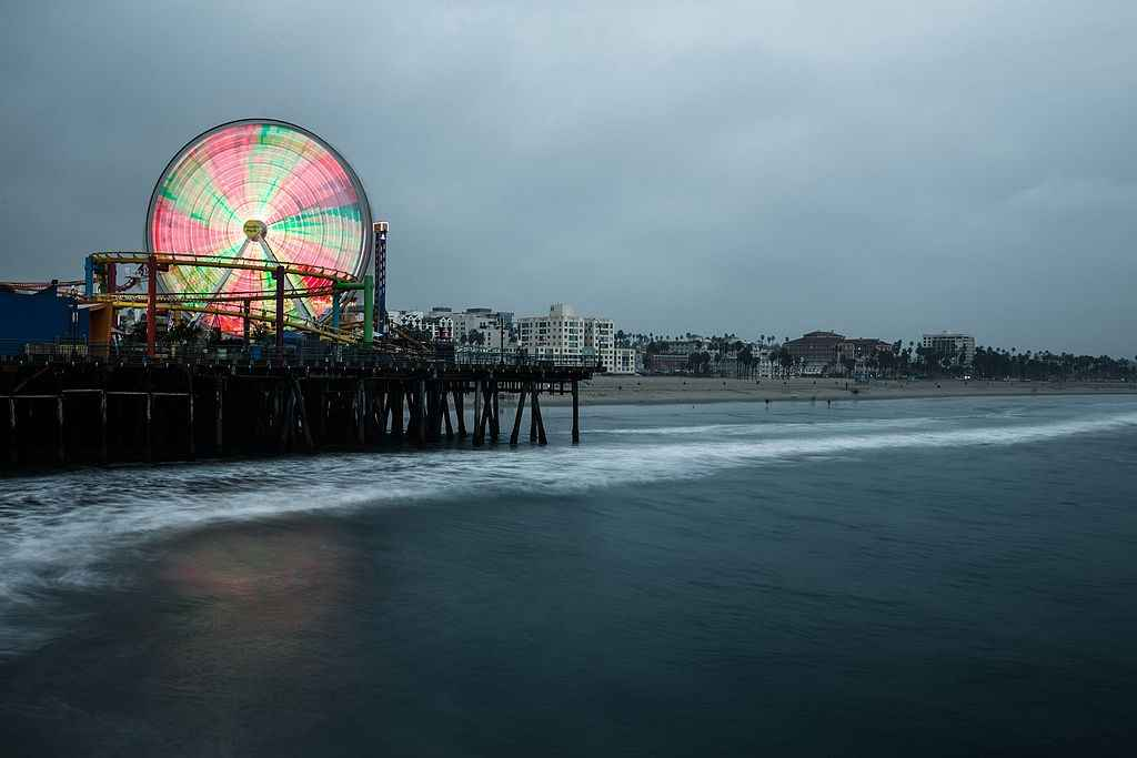 Timelapse photography of a lit-up ferris wheel at the Santa Monica Pier against a dark sky