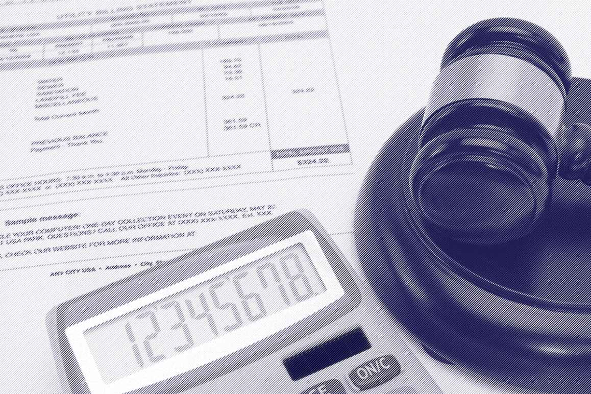 A gavel next to a bill and a calculator