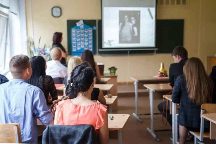 A school classroom with a teacher at standing at the blackboard with a projector screen and students sitting at their desks.