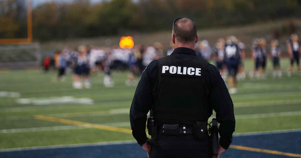 School police overlooking students at football practice