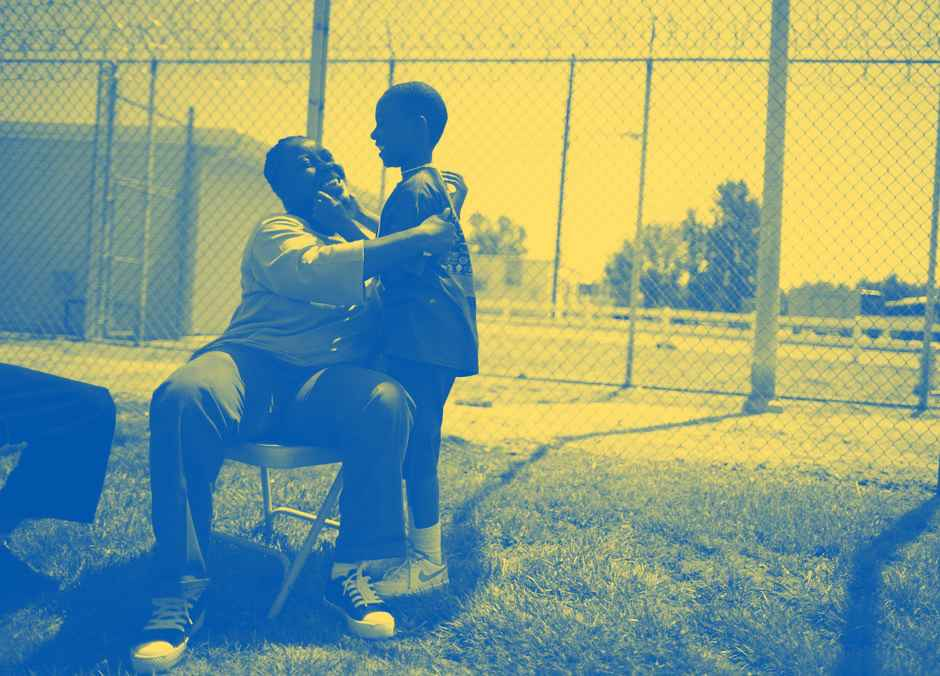 A woman sitting on a chair in a prison courtyard, embracing her young son
