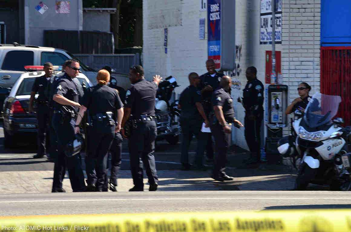 8 police officers standing on a street outside, yellow police tape in the foreground.