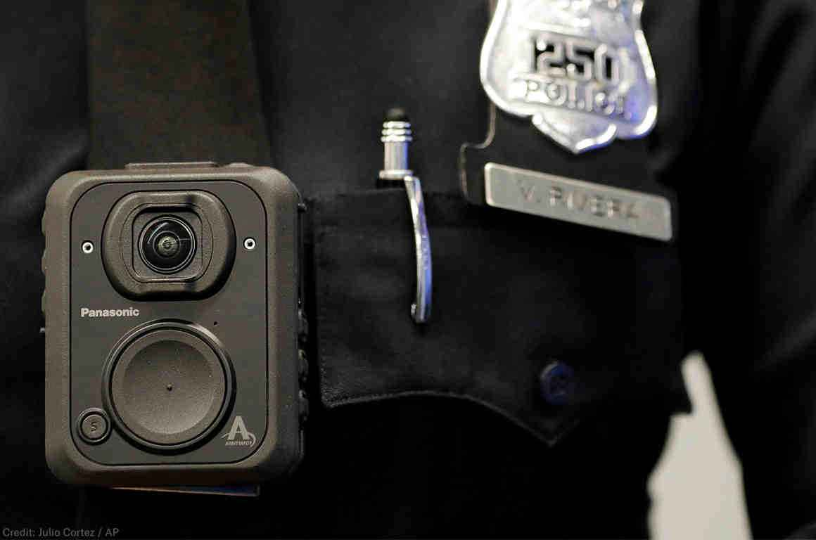 Police body camera pinned to the front of a police officer's shirt, a police badge to the left