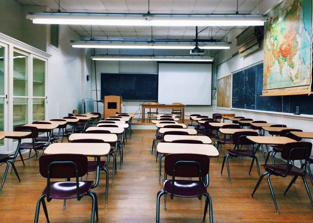 A classroom with five rows of school desks, a blackboard at the far end of the room, and a big world map to the right of the room
